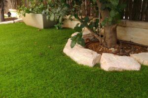דשא סינתטי לגינה עם תוחם אבן